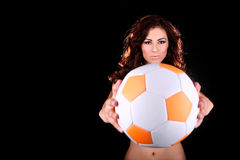 Den sexiga unga kvinnan med en fotboll klumpa ihop sig Royaltyfri Foto