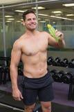 Den Shirtless kroppsbyggaren som dricker sportar, dricker att le på kameran Arkivbilder