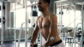 Den Shirtless muskulösa mannen som gör kabel, korsar över bröstkorgövning på idrottshallen lager videofilmer