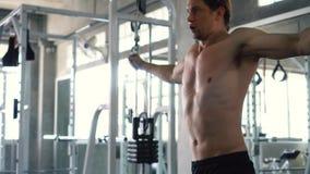 Den Shirtless muskulösa mannen som gör kabel, korsar över bröstkorgövning på idrottshallen stock video