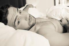 Den Shirtless sexiga hunky mannen med skägget ligger naket i säng fotografering för bildbyråer