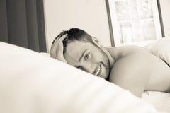 Den Shirtless sexiga hunky mannen med skägget ligger naket i säng royaltyfria bilder