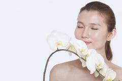 Den Shirtless unga kvinnan med ögon stängde att lukta en grupp av härliga vita blommor, studioskott Fotografering för Bildbyråer