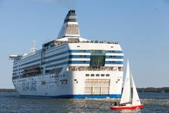 Den Silja Line färjan och den lilla segelbåten seglar från port av Helsingfors Arkivbilder