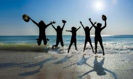 Den Sillhuettes flickan hoppar på stranden fotografering för bildbyråer