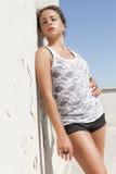 Den sinnliga brunetten garvade flickabenägenhet på en vägg varm sun Fotografering för Bildbyråer