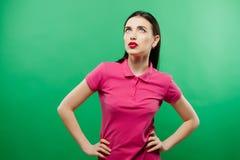 Den sinnliga brunetten i rosa skjorta med ljus makeup poserar i studio på grön bakgrund royaltyfria foton