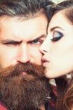 Den sinnliga kvinnakyssen uppsökte mannen, förälskelse Kvinna med makeuphud och hipster med det långa skägget Koppla ihop förälsk arkivfoton