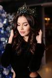 Den sinnliga kvinnan bär den eleganta klänningen som poserar bredvid den dekorerade julgranen Arkivfoto