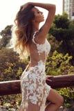 Den sinnliga kvinnan med blont hår i lyxigt snör åt klänningen Arkivbild