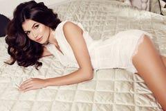 Den sinnliga kvinnan med långt mörkt hår bär den eleganta klänningen som poserar på sovrummet Arkivfoton