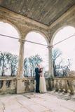 Den sinnliga maken och frun som kramar under farstubron, välva sig i antikviteten fördärvad slott arkivfoto