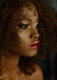 Den sinnliga ståenden av den kvinnliga modellen för den magiska overkliga guld- afrikanska amerikanen med ljust blänker makeup, g Arkivfoton