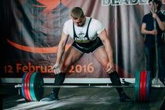 Den sista idrottsman nen för den unga mannen för försöket utför deadliftskivstången Arkivfoto