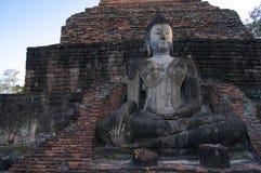 Den sittande buddha statyn av Wat Mahathat i historiska Sukhothai parkerar fotografering för bildbyråer