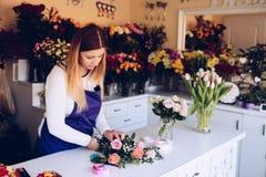 Den självständiga ägaren för den unga kvinnan av blomsterhandlaren shoppar ordna buketten av rosor Arkivfoton