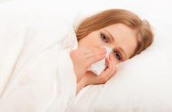 Den sjuk sjuka flickan nysar in i en näsduk i säng Fotografering för Bildbyråer