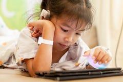 Den sjuka asiatiska flickan för det lilla barnet, som har dropplösningen, förband att spela den digitala minnestavlan för att kop arkivbild
