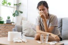 Den sjuka asiatiska unga kvinnan nyser hemma på soffan med en förkylning, henne blåser hennes näsa royaltyfri fotografi