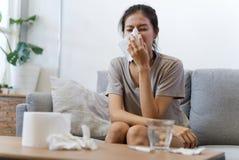 Den sjuka asiatiska unga kvinnan nyser hemma p? soffan med en f?rkylning royaltyfria foton