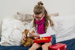 Den sjuka barnflickan i exponeringsglas, läker hans sjuka nallebjörn Arkivfoton