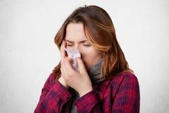 Den sjuka desperata kvinnan har influensa, den rinnande näsan, slagnäsa i näsduk, har ruskig huvudvärk, fångad förkylning efter l royaltyfri bild