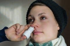 Den sjuka flickan besprutar sprejen från rinnande näsa in i det nasala passerandet Royaltyfri Foto