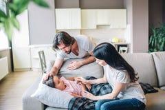 Den sjuka flickan ligger på soffan Hon täckte med filten Kvinnan rymmer termometern och blick på den Grabbhållhand på flicka` s fotografering för bildbyråer