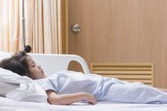 Den sjuka gulliga asiatiska flickan återställer sömn på tålmodig säng i t Royaltyfri Bild