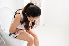 Den sjuka kvinnahållen smärtar magen i toalett fotografering för bildbyråer
