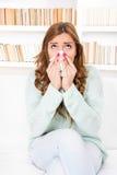 Den sjuka kvinnan fångade förkylning som blåser hennes näsa in i näsduken royaltyfri bild