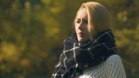 Den sjuka kvinnan i halsduk som hostar och nyser i höst, parkerar, fångade förkylning, immunitet arkivfilmer