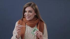 Den sjuka kvinnan mäter temperaturen och leendena lager videofilmer