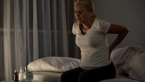 Den sjuka kvinnan som trycker på hennes baksida och att sitta på säng på natten som lider från, smärtar royaltyfri foto