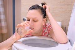 Den sjuka kvinnan spyr i toaletten som hemma sitter på golvet, tecknet för matförgiftning royaltyfria foton