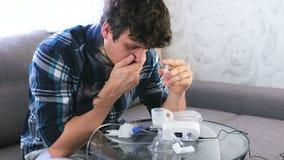 Den sjuka mannen h?ller saltdammet fr?n injektionssprutan in i beh?llaren f?r inhalatorn lager videofilmer
