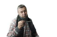 Den sjuka mannen mäter temperaturen arkivbild
