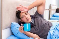 Den sjuka mannen med influensa som ligger i sängen arkivbilder
