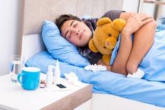 Den sjuka mannen med influensa som ligger i sängen royaltyfri bild