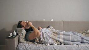 Den sjuka mannen plaskar en medicin i näsan, medan ligga på soffan hemma lager videofilmer