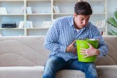 Den sjuka mannen som hemma lider från infektion och den dåliga magen arkivfoton