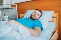 Den sjuka mannen som sover på sjukhussäng på, avvärjer, säng för sjukhuspatienten royaltyfri bild