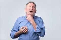 Den sjuka mogna mannen med smärtar i hals arkivfoton