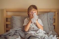 Den sjuka pojken hostar och torkar hans n?sa med torkar Sjukt barn med feber och sjukdom i s?ng royaltyfria foton