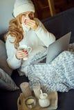 Den sjuka unga härliga blondinen på en soffa med en filt och bärbara datorn och rånar av te royaltyfri foto