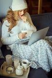 Den sjuka unga härliga blondinen på en soffa med en filt och bärbara datorn och rånar av te royaltyfria foton