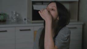 Den sjuka unga kvinnan dryper nasal droppe till näsan i köket på natten Behandling av rhinitis hemma lager videofilmer