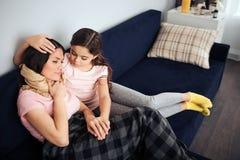 Den sjuka unga kvinnan sitter på soffan samman med hennes dotter Huvud för barnomfamningmoder Hon ser henne Ungehandlagkvinna arkivfoto