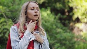 Den sjuka unga kvinnan som bär dåligt lidande för röd halsdukkänsla från halsen, smärtar och att stå i parkerar Smärtsamt svälja stock video
