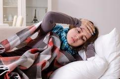 Den sjuka unga kvinnan som hemma lider royaltyfria foton